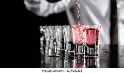 Pink cocktails at the bar. Cocktail set at the night club. Professional  bartender pours alcoholic drink into small glasses on bar. Close up of pink cocktail splash.