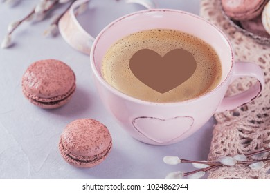 Pink coffee mug with sweet pastel french macaroons and pussy willow on light table from above. Breakfast on Mothers day or Women's day. Tender spring background.