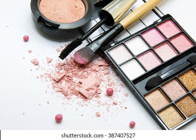 pink collection of makeup products on white background with space for text