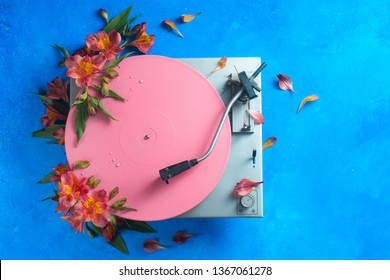 Pink color block flat lay with colorful vinyl record player and flowers. Spring music still life concept on a blue background with copy space