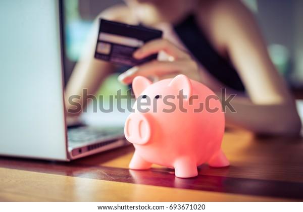 Rosa Farbe Schweinefleisch sparen Bank mit Frau, die eine Kreditkarte über Internet-Computer auf dem Hintergrund hält, Geld sparen Einkauf online Konzept.