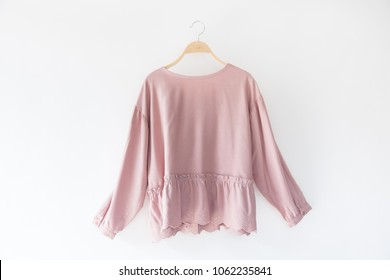 Pink color woman clothes hanging on white background.