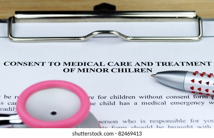 A pink colored stethoscope on a metal clipboard along with a ball point pen resting on a medical consent form for a minor, ready for you to sign.