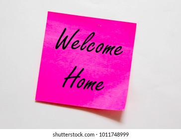 "A pink coloured sticky note pad isolated with the message of ""Welcome Home"" on an off white background"