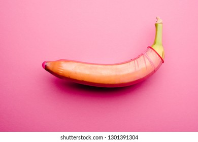 Pink condom on banana in front of pink