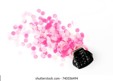 Pink confetti falling out of  purse on white background