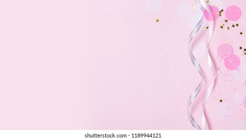 Pink confetti and stars and sparkles on pink background. Top view, flat lay. Copyspace for text. Bright and festive holiday background. For Christmas, New year, Mother's day.