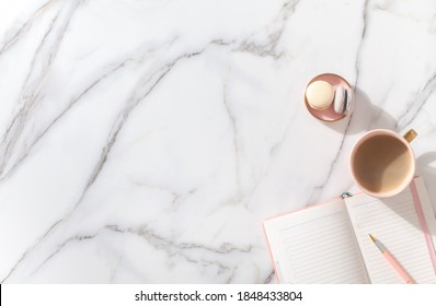 Pink coral colored diary for the year 2021, pen, coffee latte, macaron cookie and straw woven placemat on white marble background. New year planning concept. Minimalistic workstation. Copy space.