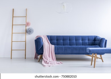 Pink coverlet thrown on the blue comfy couch in room with wooden ladder and empty white wall