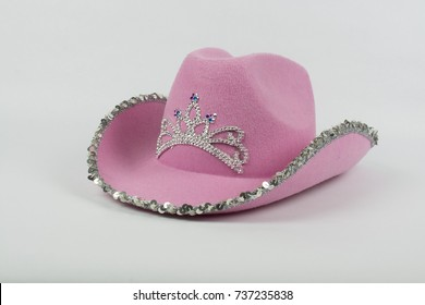 9443fc2a A pink cowboy hat with sequins and a crown sits isolated on a white  background.