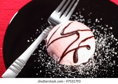Pink cream cake on a black plate with a fork on red background