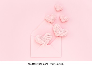 Pink crocheted hearts in envelope on pink background. Romantic congratulation on Valentine's Day. Handmade, Love confession. Flat lay, minimal holiday card.