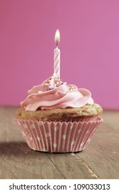 Pink cupcake with birthday candle on  wooden table