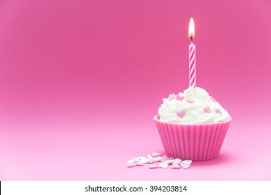 pink cupcake with candle and pink background