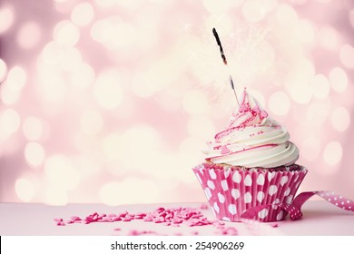 Pink cupcake with sparkler and fairy lights