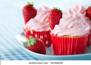 Pink cupcakes with fresh strawberries and sprinkles on a vintage tray and blue retro towel