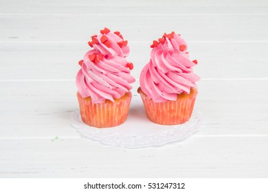 Pink cupcakes with hearts on a white wooden background. Dessert on Valentine's day