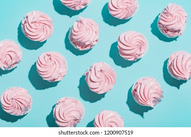 Pink cupcakes on blue background composed in a pattern. Sweet desserts. Flat lay.