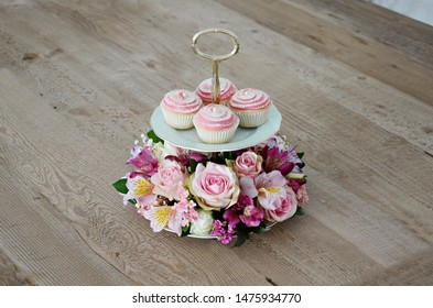 Pink cupcakes over a fresh flower arrangement over a wodden table in Goiania, Goias, Brazil