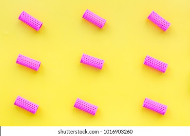 Pink curlers for hairdress. Pattern on yellow pastel background top view