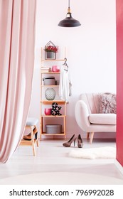 Pink curtain and black lamp in bright dressing room interior with sofa and high heels near cabinet