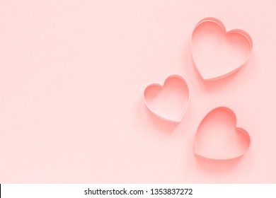 Pink cutters cookies in heart shape on pastel pink background,  Love romantic pattern, template.