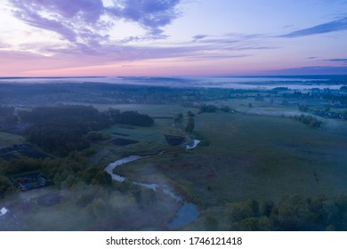 Pink dawn behind the village over the misty river. Time before dawn from a bird's-eye view.