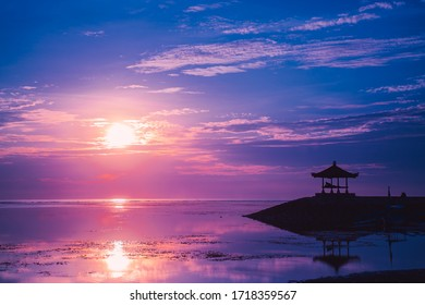Pink dawn the sun and the gazebo at Sanur beach, Bali, Indonesia. A calm surface of sea water that reflects the sun and cloudy sky. Travel destination Bali