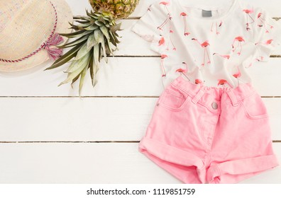 Pink denim shorts and a blouse, straw hat, pineapple. White Old Wooden Background.