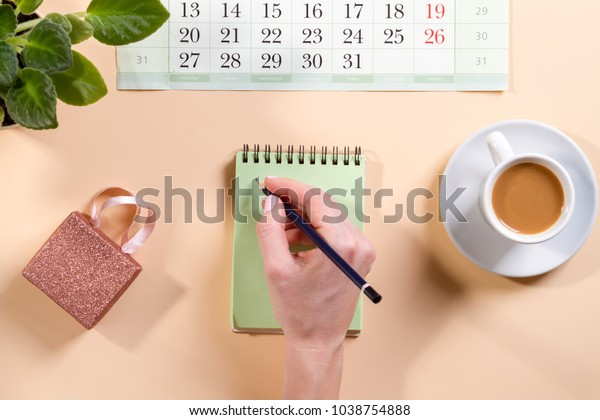 pink designer office desk table with blank notebook page with pen, calendar and cup of coffee. Top view, flat lay.