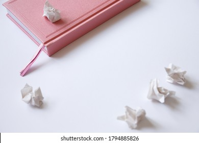 Pink diary on a white background and crumpled pieces of paper. Mistakes in the letter