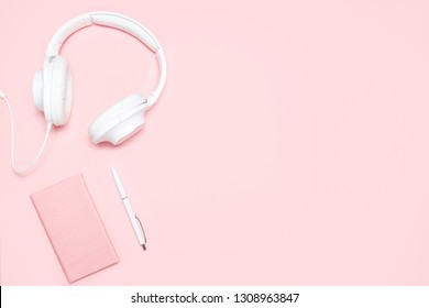Pink diary, white pen and white headphones on pink desk. Top view. Minimalistic flat lay composition with copy space for bloggers, designers, magazines etc.