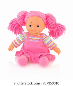 Pink doll isolated on white background with shadow reflection. Cute pink rag baby doll sitting on white underlay. Nice contemporary rag baby with pink hair. Modern joyfully rag baby.