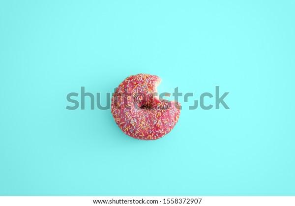 pink Donut bite blue background