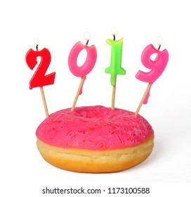pink donut with burning candles 2019 isolated over white background