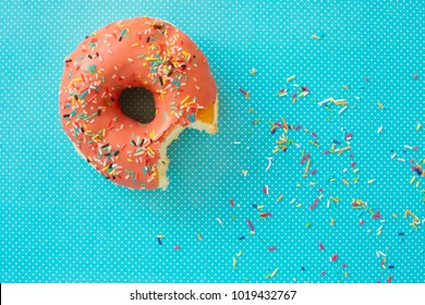 Pink donut with colorful icing on a turquoise background. Minimal concept. Candy Shop series. Glazed donut.