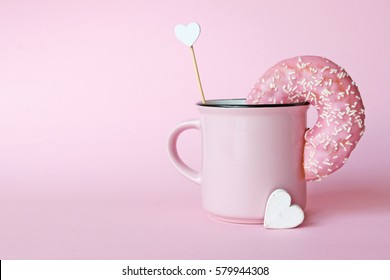 Pink donut in a cup on pink background