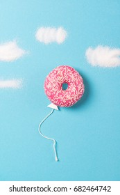 Pink donut on blue background, creative food minimalism, donut in a shape of balloon in the sky with clouds made of sugar, top view
