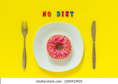 Pink donut on white plate and cutlery table knife fork Text NO DIET. Still life on yellow background. Top view Flat lay Concept No Diet day