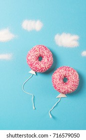 Pink donuts on blue background, creative food minimalism, donut in a shape of balloon in the sky with clouds made of sugar, top view