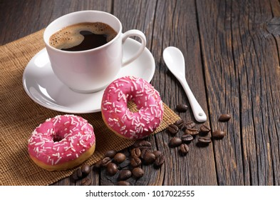 Pink donuts with sprinkles and cup of coffee on old wooden table