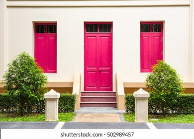 Pink Door , pink window on Cream Wall on red staircase with small tree background