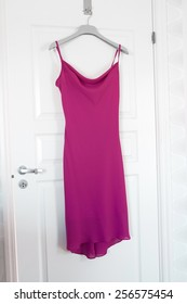 Pink Dress hanging on a door