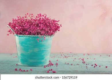 Pink dried baby's breath flowers in a blue vase on wooden vintage background
