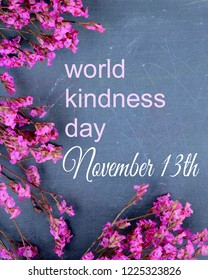 Pink dried flowers on a slate background with text for World Kindness Day on November 13th.