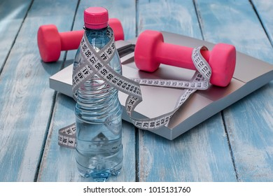 Pink dumbbells, a bottle of drinking water, a scales and a centimeter tape on a blue wooden background. Fitness concept.