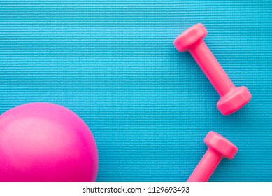 Pink dumbbells and gym ball for fitness exercise on blue yoga mat background in fitness center - Health care concept