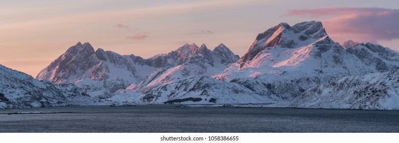 pink early morning glow light on snow covered mountains in arctic norway, super wide panoramic scene,