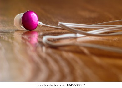 Pink earphones with white cable on wooden desk.