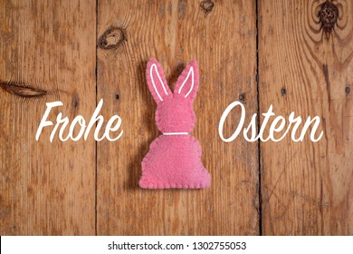 """Pink easter bunny with text """"Frohe Ostern"""" and a wooden background. Translation: """"Happy Easter"""""""